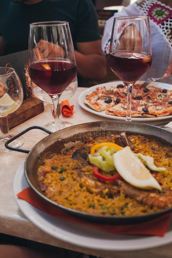 Typical spanish seafood paella in traditional pan. glasses with Spanish sangria in the background. dinner in a restaurant stock image