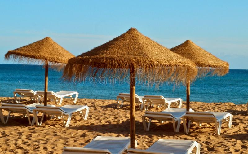 Straw umbrellas with sunbeds at the beach and sea royalty free stock photos