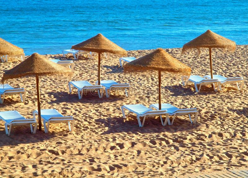 Straw umbrellas with sunbeds at the beach and sea stock image