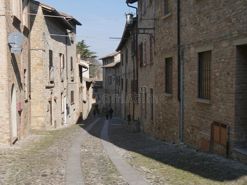 Typical street in Castell`Arquato. They were built in Medieval age with Arda river stones stock photography