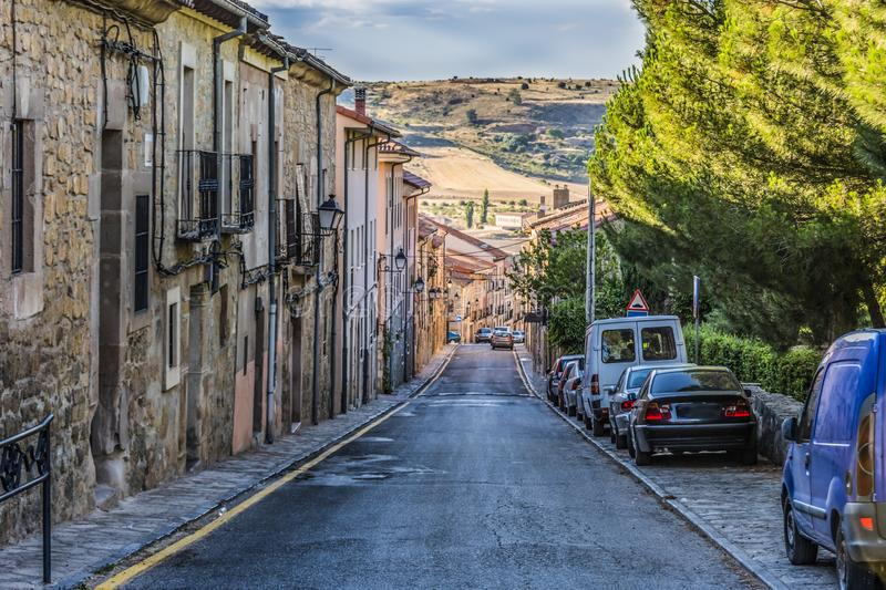 Typical street in descent in the city of Siguenza and in the background the hills of Guadalajara. Castilla La Mancha Spain stock images