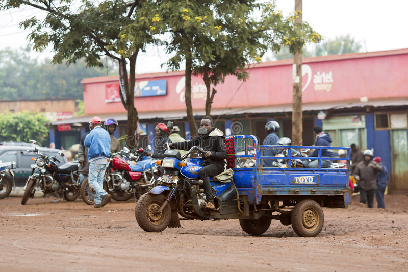 Typical street scene at Arusha in Tanzania. AFRICA, TANZANIA, MAY, 09, 2016 - Typical street scene in Arusha. A series of motobikes are parked in front of the stock image