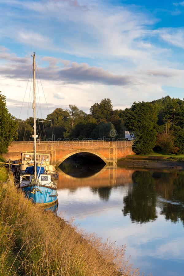 A typical Suffolk scene of a sail boat moored up on the rivers edge with a brick bridge in the background with the reflection in. A sail boat moored up on the stock images