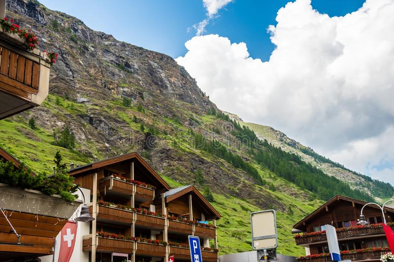 Typical Swiss Wooden chalets amid magnificent mountainsin canton of Valais, Switzerland in summer. Typical Swiss Wooden chalets amid magnificent mountainsin royalty free stock image