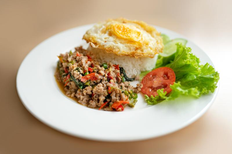 Popular Thai meal - rice topped with stir-fried pork and basil and fired egg stock photos