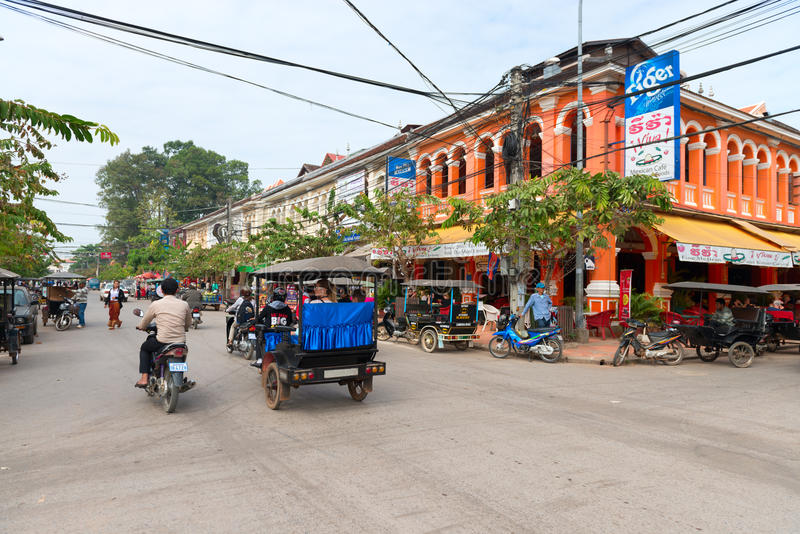 Typical traffic passes a colorful building in Siem Reap, Cambodia. SIEM REAP, CAMBODIA - 23 DEC 2013: Typical traffic passes a colorful building in Siem Reap stock image
