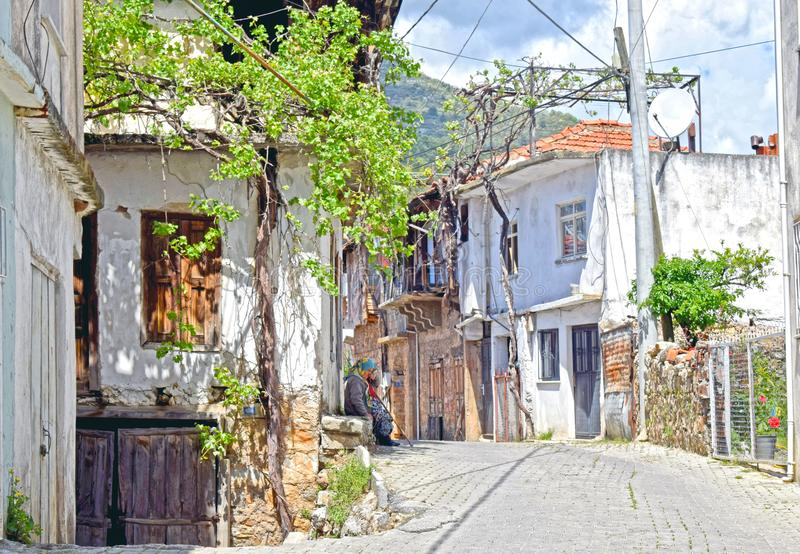 A typical Turkish village with a lady sitting on the door step stock photo
