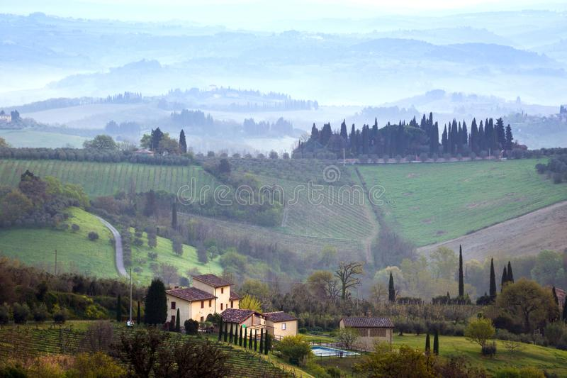 Typical Tuscan landscape. A view of a villa on a hill, a cypress alley and a valley with vineyards, province of Siena. Tuscany, Italy stock image