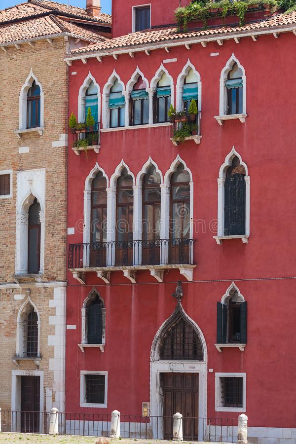 Typical venetian building, red walls with white gothic windows stock photos