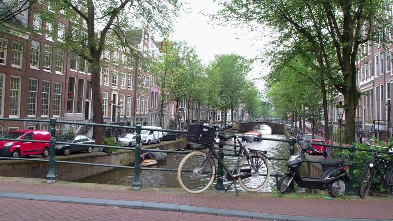 Typical view over the bridges and canals in the canal belt of Amsterdam - AMSTERDAM - THE NETHERLANDS - JULY 19, 2017. Typical view over the bridges and canals royalty free stock photo