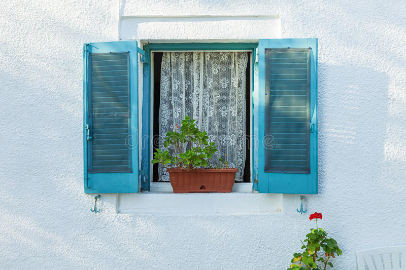 Typical window with blue shutters on white wall. Open window with blue shutters on white wall and flowers, Corfu, Greece royalty free stock photography