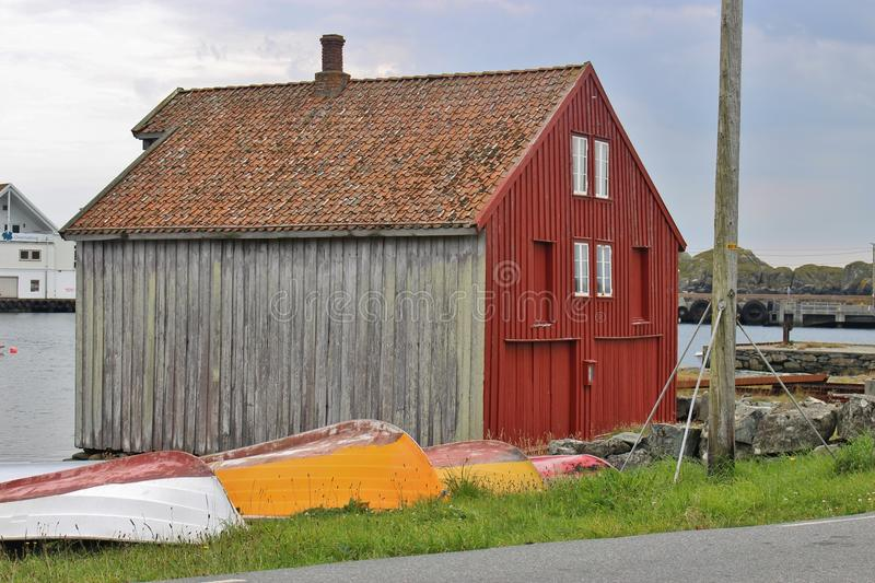 Typical wood house in Norway with colorful boats. On the south port of the small island Utsira in Norway, Europe. Utsira lies in the North Sea, about 18 royalty free stock image