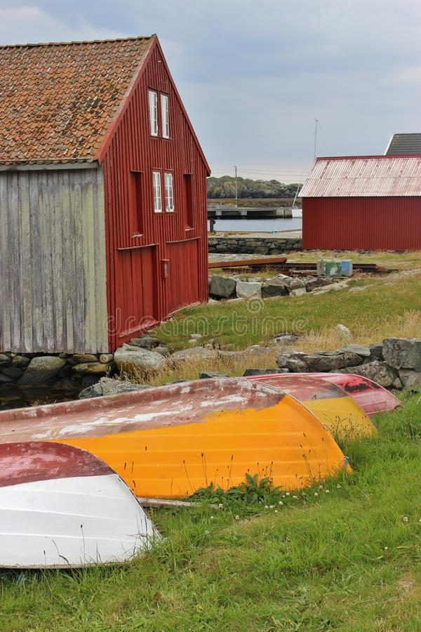 Typical wood house in Norway with colorful boats. On the south port of the small island Utsira in Norway, Europe. Utsira lies in the North Sea, about 18 stock photography