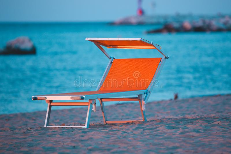 Typical yellow or orange sunbeds of the Riviera Romagnola adriatic coast of Italy, with the sea in the background. Rimini Beach.  stock photography