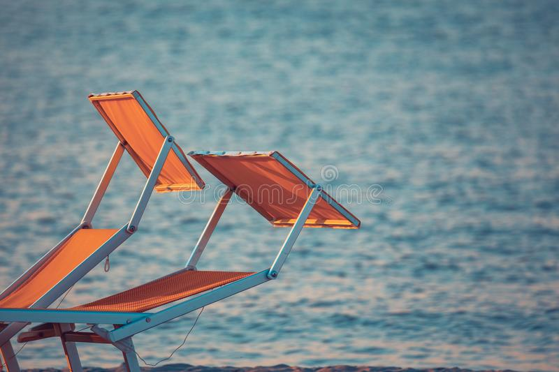 Typical yellow or orange sunbeds of the Riviera Romagnola adriatic coast of Italy, with the sea in the background. Rimini Beach.  royalty free stock photos