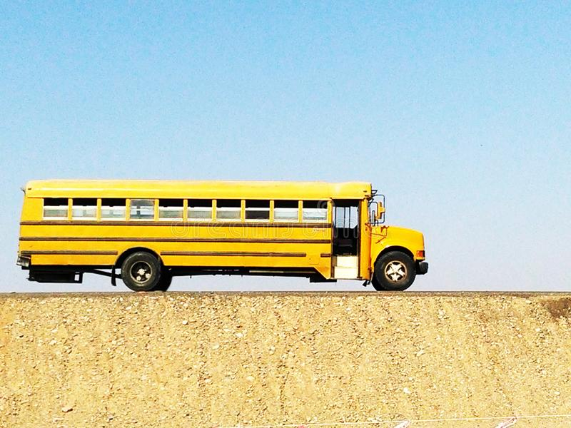 Typical yellow school bus for transfer of labor personnel in the desert of saudi arabia. Transport concept royalty free stock photos
