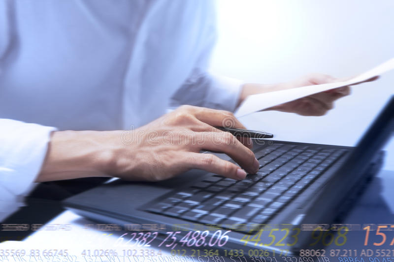 Typing. Businessman typing on notebook and running numbers royalty free stock image