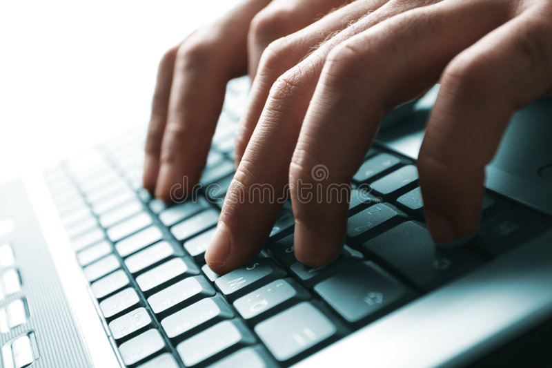 Typing. Male hands typing on a laptop