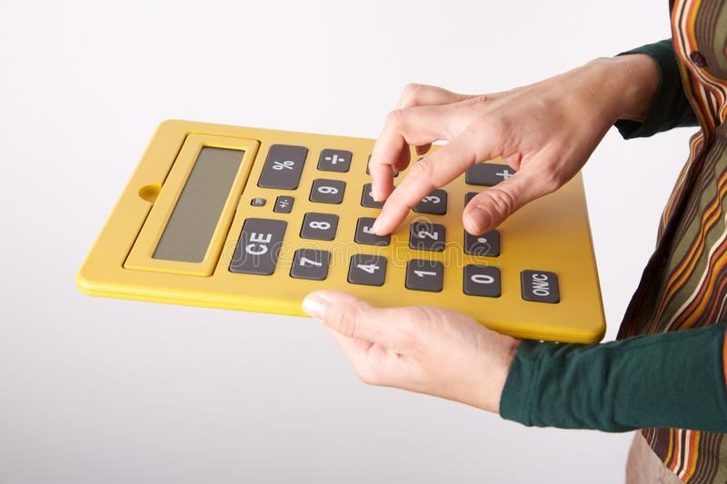 Typing on big yellow calculator royalty free stock images