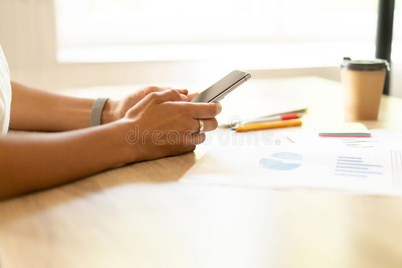 Typing business message. Close-up of young woman in formalwear holding mobile phone while sitting at her working place. Typing business message. Close-up of stock images