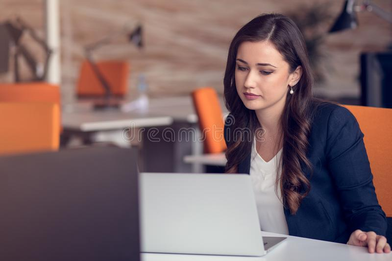 Typing business message. Confident young woman in smart casual wear holding smart phone and looking at it with smile stock photos