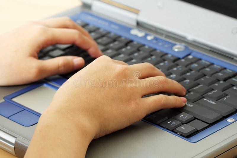 Typing on laptop stock image