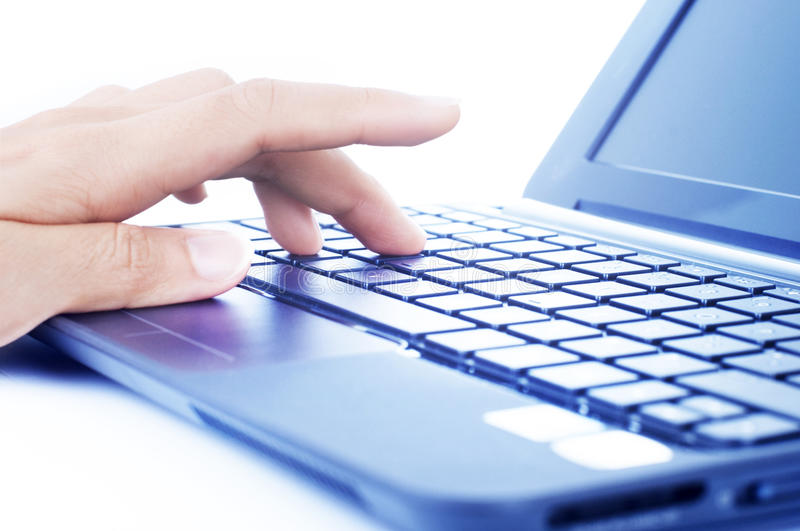 Typing on a Laptop Keyboard. Closeup of a hand typing on laptop keyboard