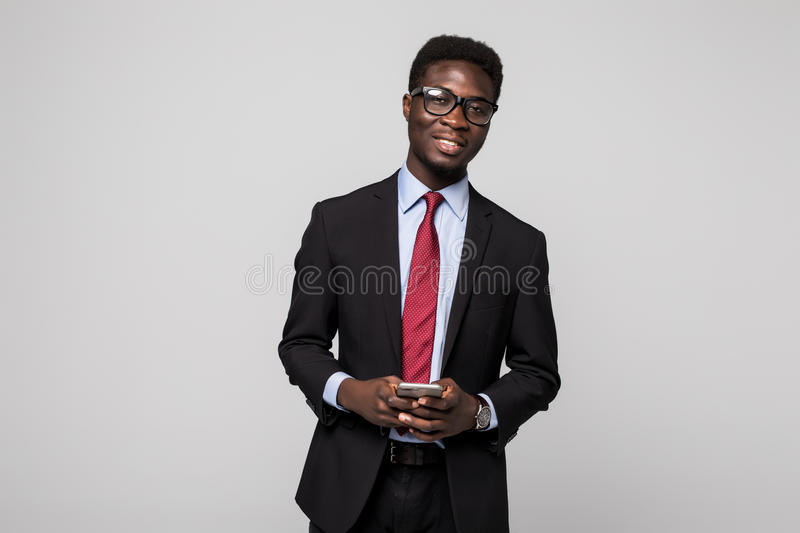 Typing a message. Cheerful black manin suit typing something on the mobile phone and smiling while standing on grey stock images