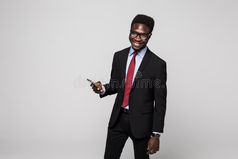 Typing a message. Cheerful black manin suit typing something on the mobile phone and smiling while standing on grey royalty free stock photo