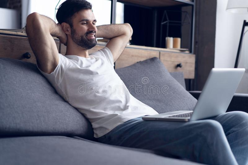 Typing new blog post. Side view of handsome young man using his laptop with smile while sitting on the couch at home. Typing new blog post. Side view of stock image