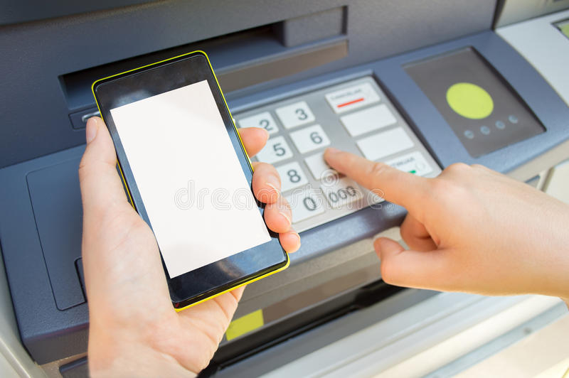 Typing security code. Man typing security PIN code you see on your phone the ATM to withdraw money stock photos