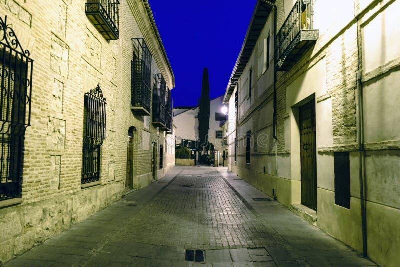 Typisch cobbled straat met voorgevels van oude huizen tijdens het blauwe uur in Alcala DE Henares, Spanje Zonder mensen en met ze royalty-vrije stock foto's