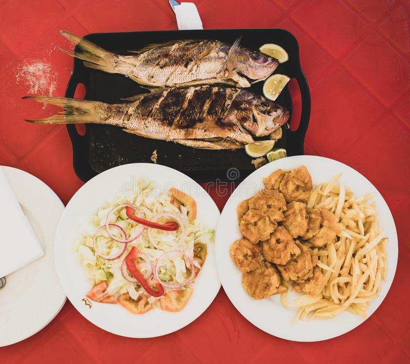 Typisch Dominicaans voedsel tijdens lunch op het strand: geroosterde vissen met salade, gebraden gerechten en tostones gebraden p stock afbeelding