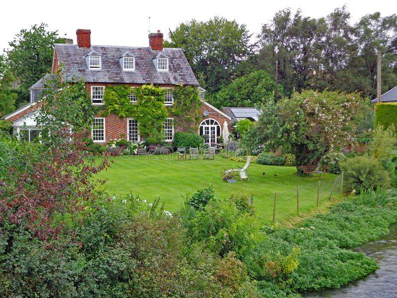Typisch Engels plattelandshuisje op summersday omringd door de dorpsstroom met een glanzende tuin stock foto