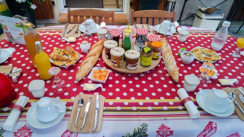 Typisch Frans ontbijt in de Provence Lijst met rood tafelkleed, baguette, jam, kaas, koffie en jus d'orange stock foto