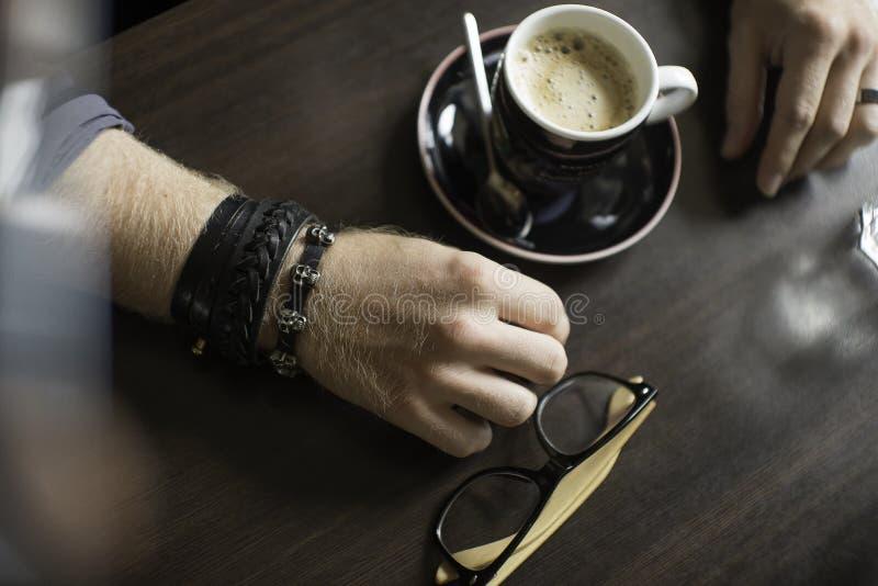 Typisch koffieterras met kop van coffe op de lijst De handen van de mens `s royalty-vrije stock fotografie