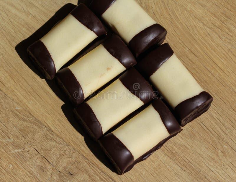 typisch Nederlands zoet geroepen koekje & x22; mergpijpje& x22; behandeld met witte marsepein, op een houten achtergrond stock afbeelding