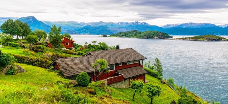 Typisch plattelands Noors landschap met rode geschilderde huizen op de kust van de fjord Bewolkte de zomerochtend in Noorwegen, E royalty-vrije stock foto