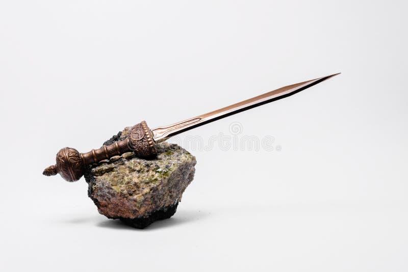 Typisch Roman zwaard op groene rots stock fotografie