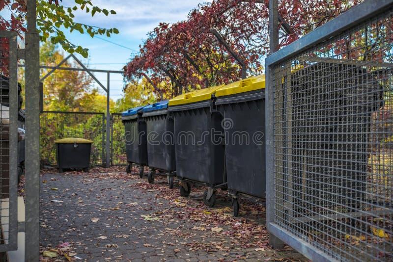 Typisch voor Duitsland, een plaats voor gescheiden inzameling van huisvuil in een gesloten gebouw dichtbij een huis stock afbeelding