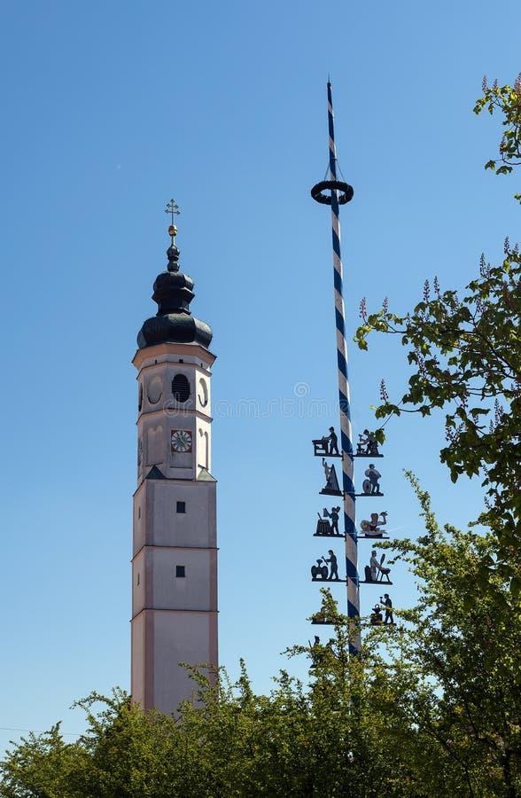 Typische Beierse kerktoren en een traditionele maibaum, maypole stock afbeelding