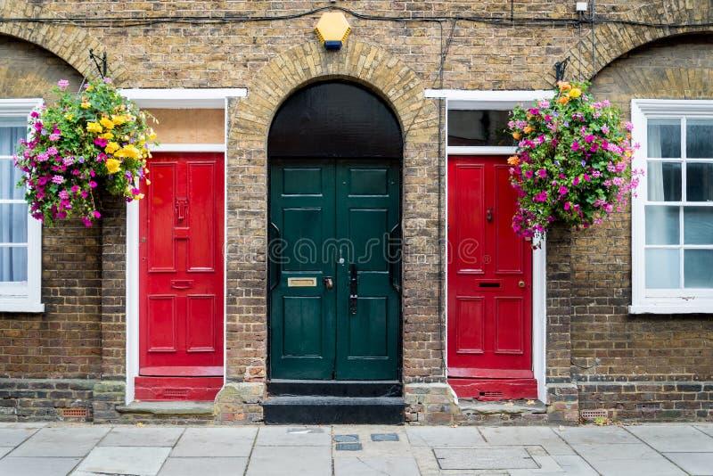 Typische britische Türen mit Türklingel in London Zwei colorfull Türen lizenzfreie stockfotografie