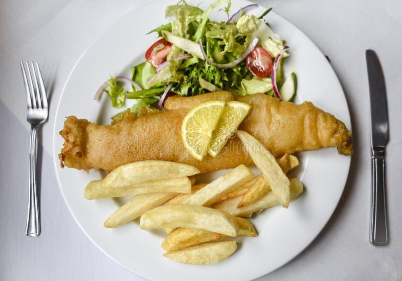 Typische Britse vis met patat: Schelvissen, gebraden gerechten en salade op witte plaat royalty-vrije stock foto