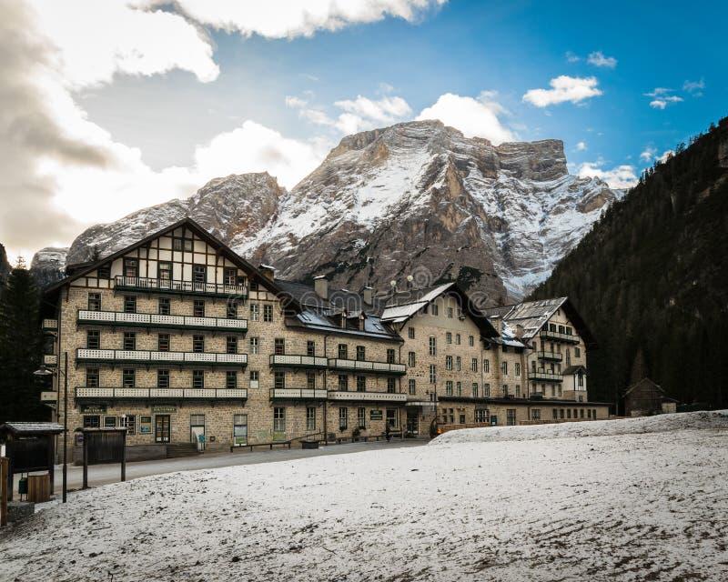 Typische Gebirgsarchitektur und schneebedeckter Gebirgszug im Ba stockfotografie