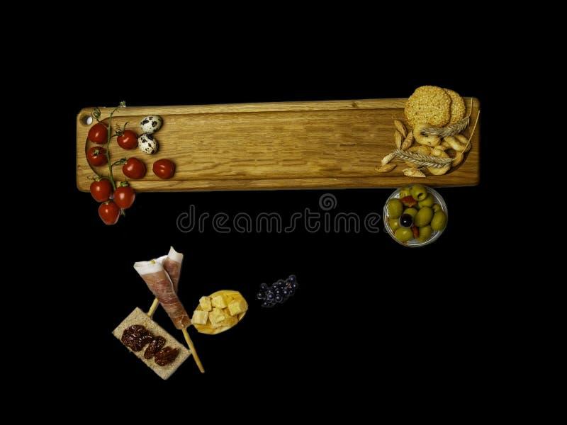 Typische Italiaanse antipasto, houten scherpe raad met prosciutto, ham, kaas en olijven op zwarte achtergrond Hoogste mening met  royalty-vrije stock foto