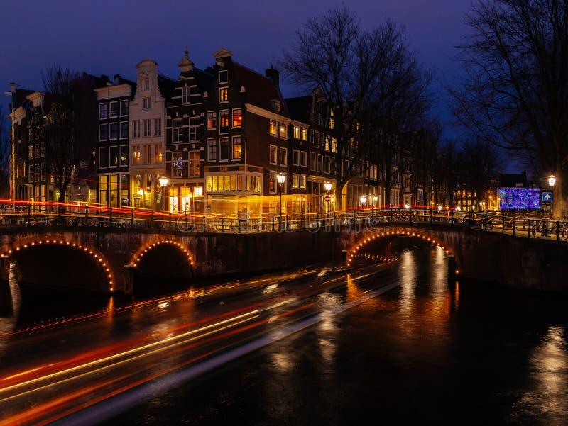 Typische Kanallandschaft Amsterdams nachts mit hellen Spuren und reflektierendem Wasser stockfotos