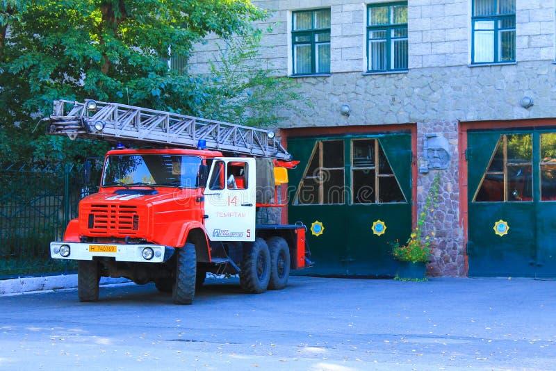 Typische Levensstijl Kazachstan De bouw van centraal Brandweerkorps en traditionele rode Brandvrachtwagen met binnen brandweerlad stock afbeelding