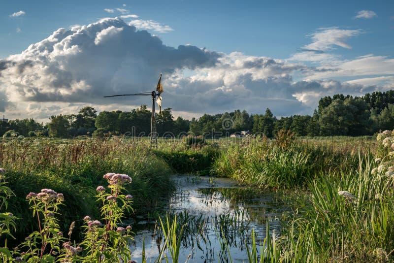 Typische niederländische pumpende Windmühle in der niederländischen Landschaft mit ihr ist viele Kanäle, Kumuluswolken im Hinterg stockbild