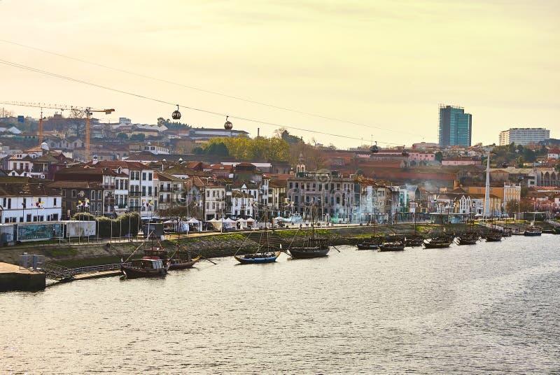 Typische Portugese houten boten, genoemd ?barcosrabelos die ?wijnvatten op de rivier Douro met mening over Villa Nova DE G vervoe stock fotografie