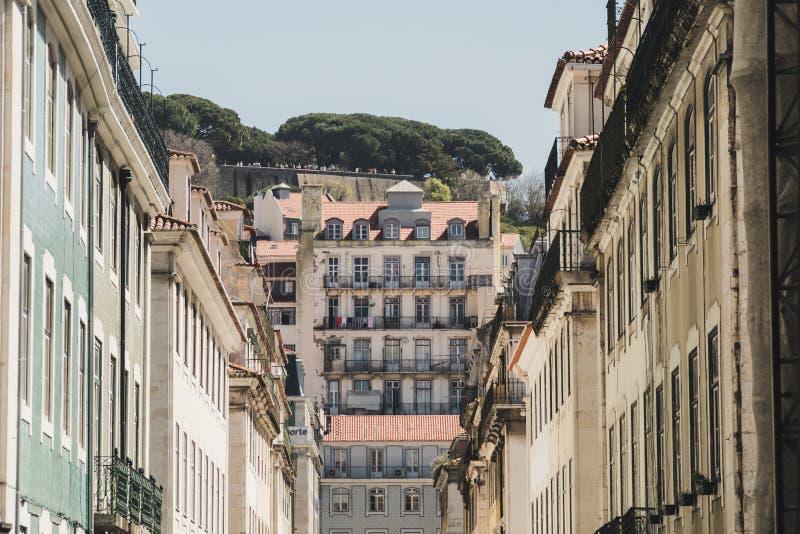 Typische straat van Lissabon van de binnenstad, Portugal Op de achtergrond, op een heuvel, zijn er mensen die op één van de muren royalty-vrije stock foto's